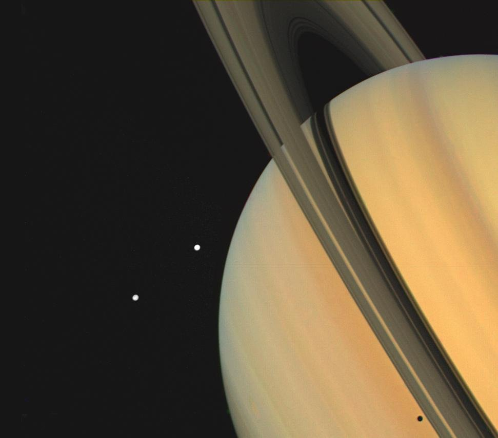 Saturn mit den Monden Tethys und Dione. (NASA/JPL)